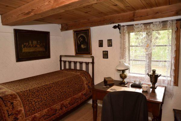 pokój nauczyciela z łóżkiem z metalowym stelażem, biurkiem z lampą naftową i gazetą
